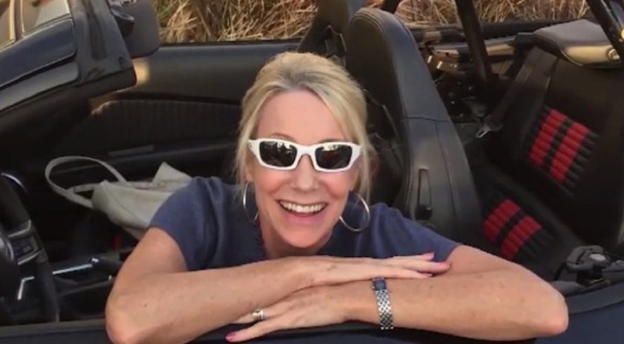 mulher de óculos apoiada na janela de carro