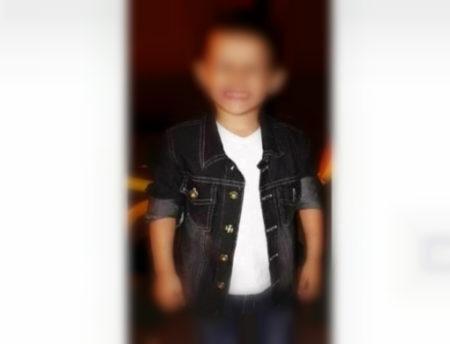 Foto de uma criança sorridente, com o rosto desfocado