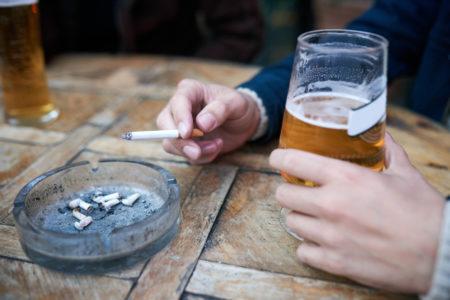 homem fumando cigarro e bebendo cerveja