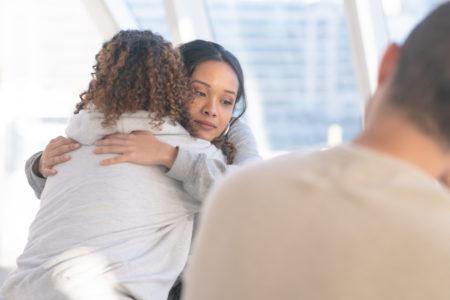 um mulher abraça outra em roda de conversa sobre dependência química
