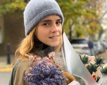 Emma Watson de touca azul e flores nas mãos