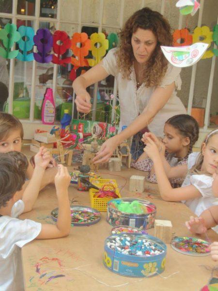 mulher brinca com crianças em feirinha de natal com presentes