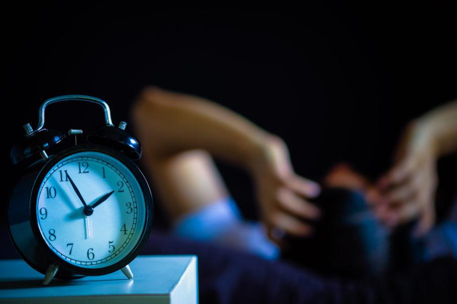 homem dormindo ao lado de despertador
