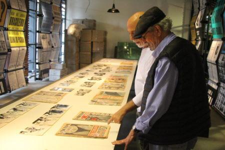 dois homens olham capas de jornal na montagem da exposição o pasquim 50 anos no sesc ipiranga