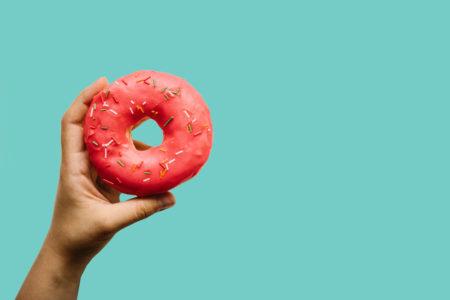 mão segurando um donnuts rosa