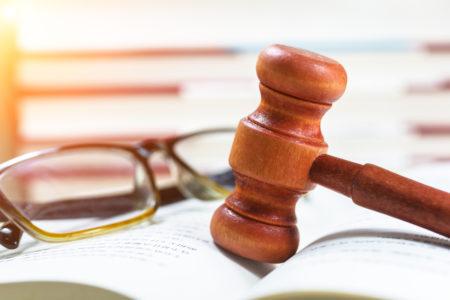 martelo de um juiz sobe um livro ao lado de um óculos