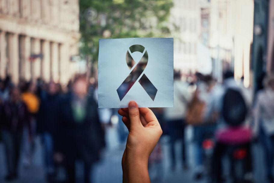 uma mão segurando o símbolo da aids no meio da multidão
