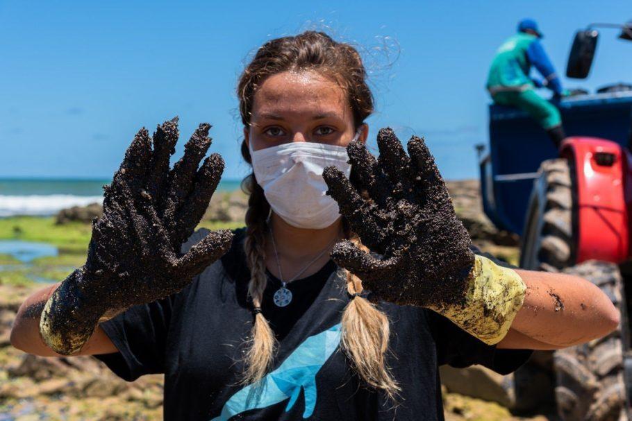 voluntária com óleo do nordeste nas mãos