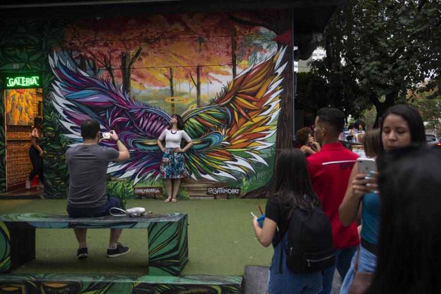 mulher posando para foto em frente a graffiti no beco do batman