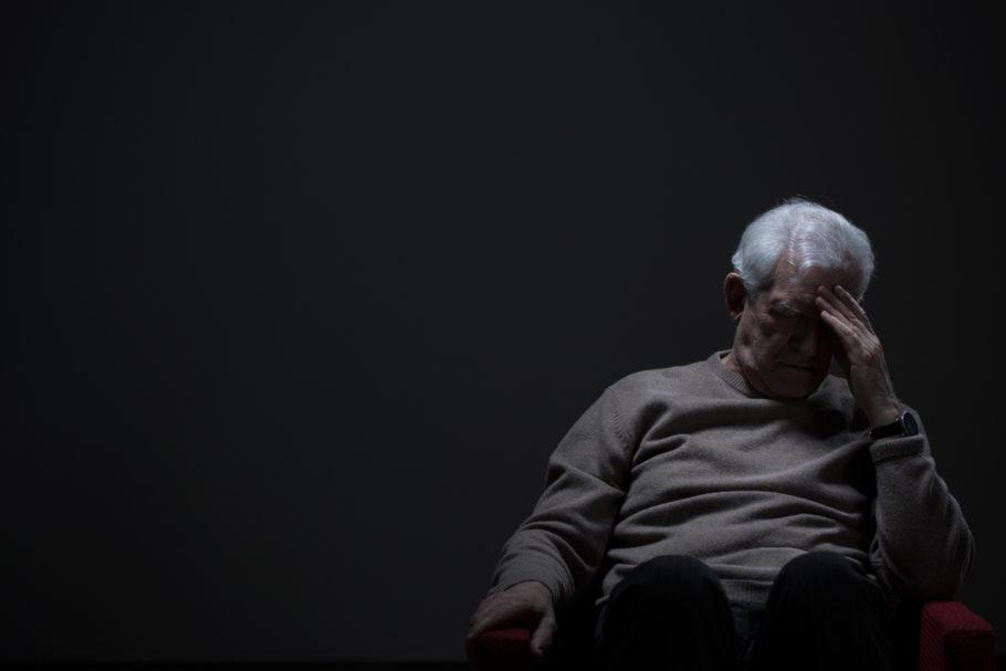 homem idoso com a cabeça baixa em um local escuro