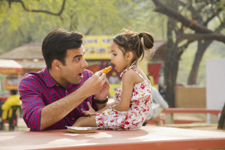 pai dando comida na boca de menina