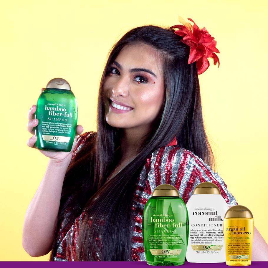 mulher com cabelo liso segurando um produto da OGX