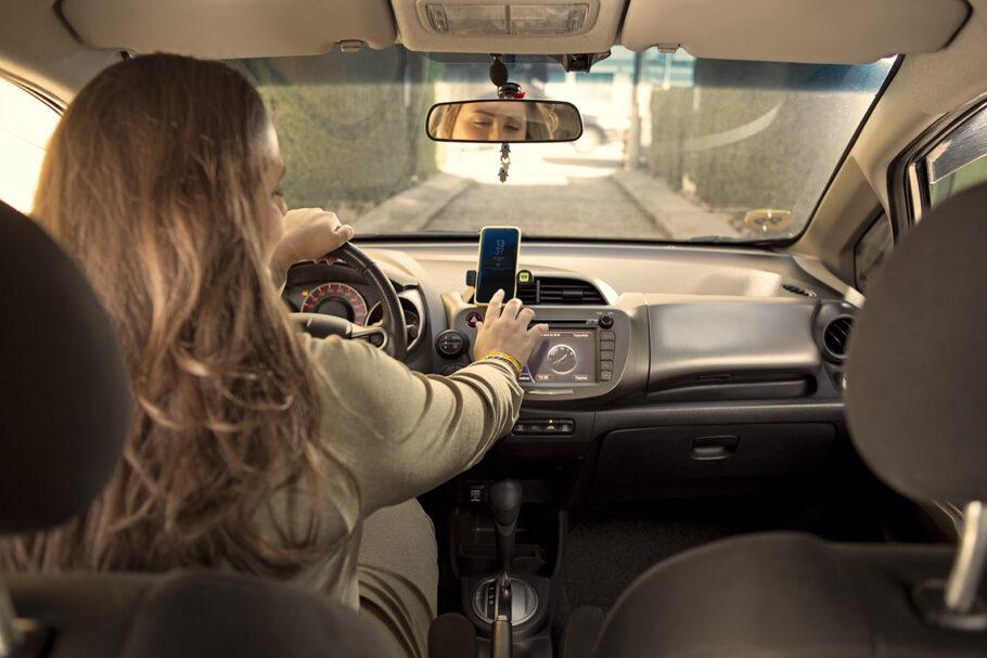 mulher dirige e mexe em celular
