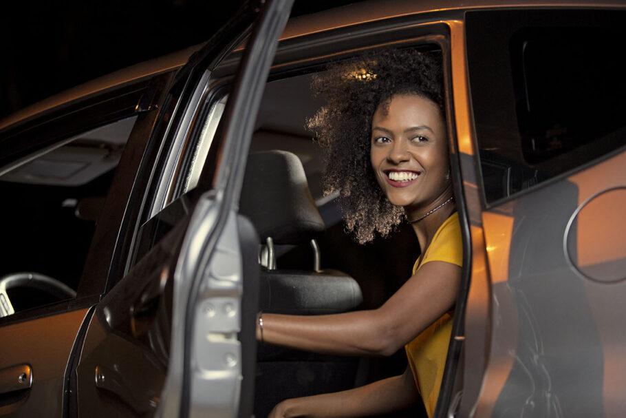 mulher dentro de carro com a porta aberta