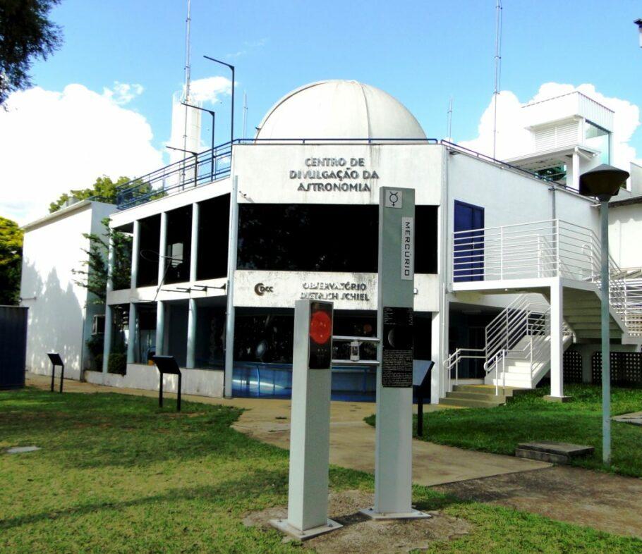 vista frontal do prédio do Observatório Dietrich Schiel. Em primeiro plano, um dos totens do Sistema Solar em escala, abordando o planeta Mercúrio