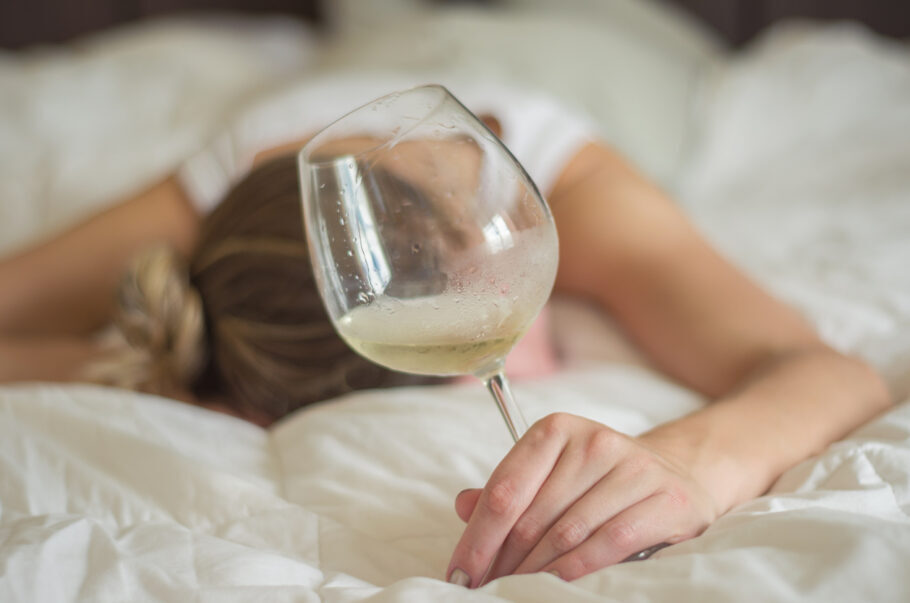 mulher deitada na cama com um copo de bebida na mão