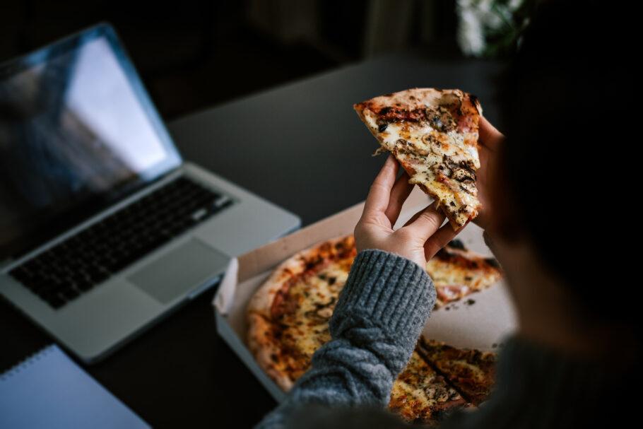 mulher comendo pizza em frente ao computador