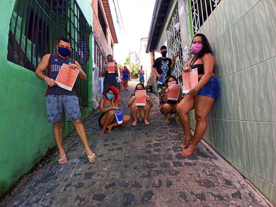 voluntários espalham cartazes na favela