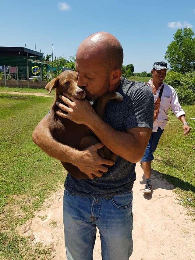 homem abraça cachorra no colo
