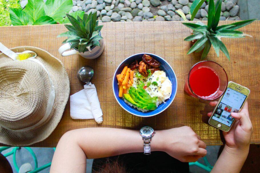 mulher comendo e olhando o celular