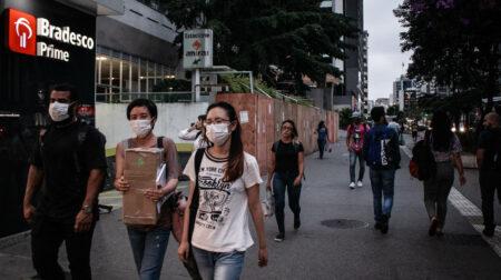 Protegidos com máscaras por causa da pandemia do coronavírus, paulistanos caminham na avenida Paulista