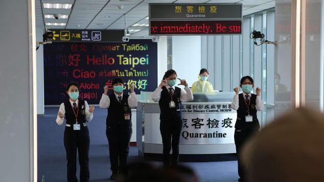 Funcionários do aeroporto de Songshan, em Taipei (Taiwan), orientam passageiros