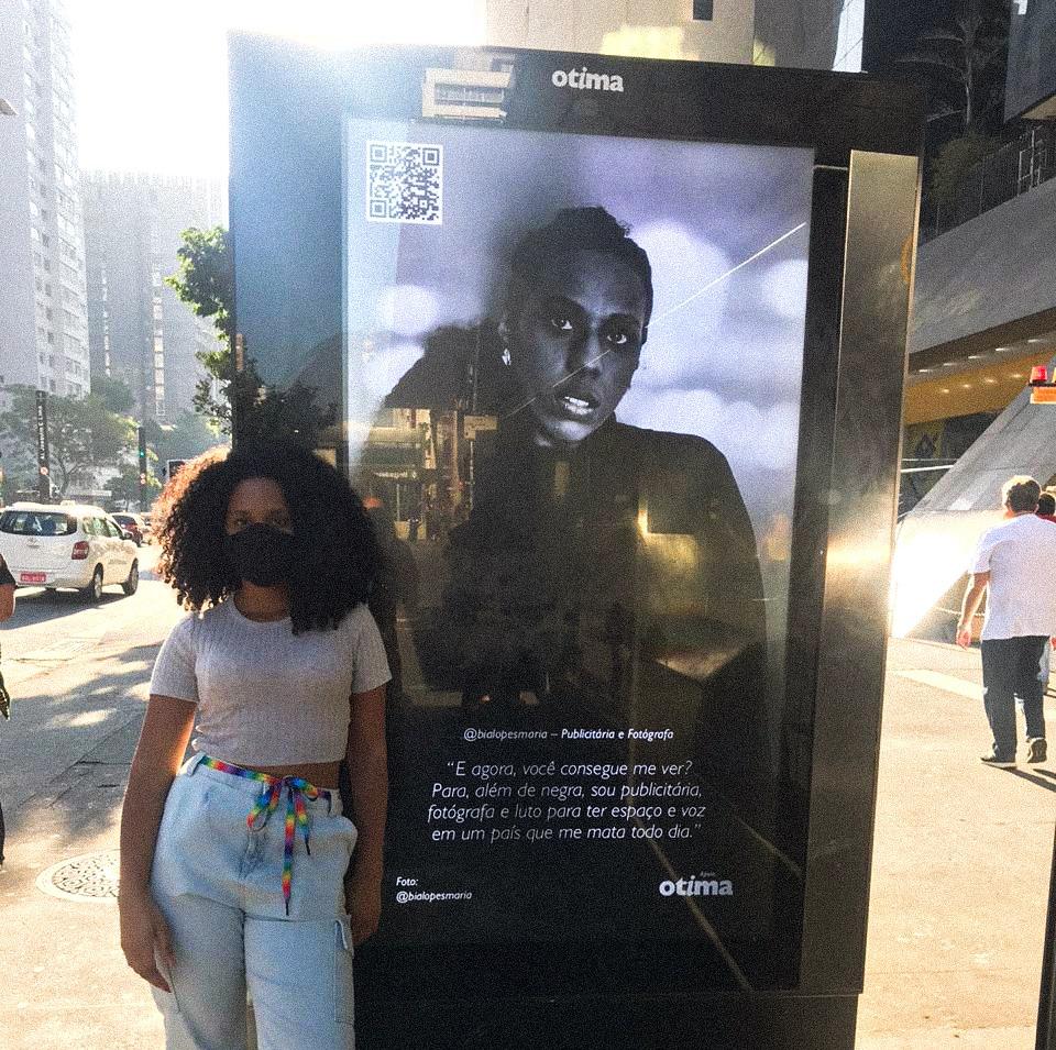 Bia Lopes (a fotografá) em frente ao seu painel