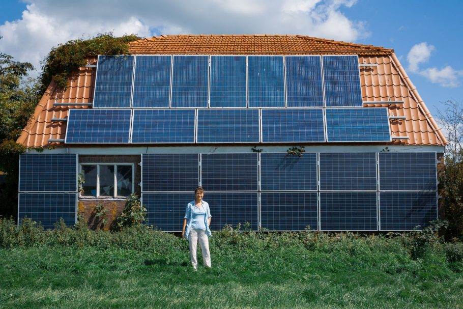 """Cena do filme """"We The Power"""" - Casa com painéis de energia solar no telhado e paredes externas."""