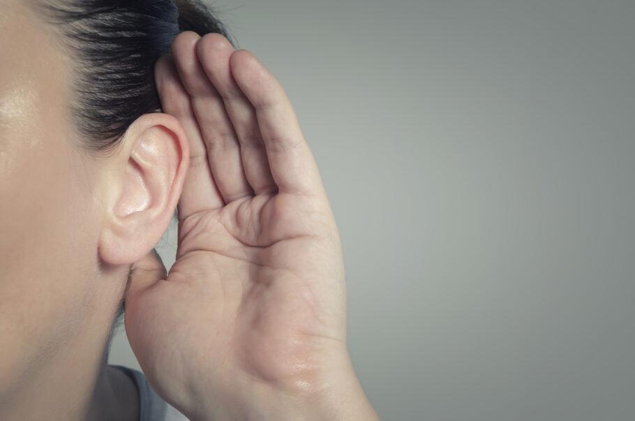 mulher com a mão no ouvido