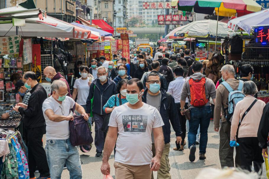 pessoas andando na rua de máscara