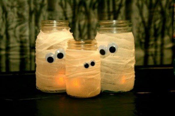 Use potes de rosquear e tire as tampas. Enfaixe-os com gaze e cole olhos de plástico. Depois, é só colocar velas dentro dos potes para criar um efeito 'assustador'.