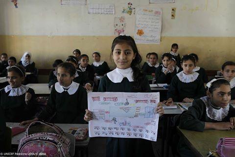A pequena Nada, de 9 anos, levanta o seu desenho de como seria a escola ideal, com belas cortinas, luz do sol  e janelas para proteger da chuva.