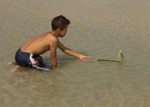 Folha de coqueiro vira barquinho nas mãos de menino.