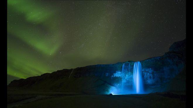 Uma noite clara criou o ambiente para esta foto da aurora boreal sobre a gigantesca cachoeira de Seljalandsfoss, na Islândia