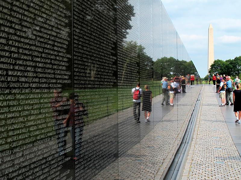 O memorial com os nomes dos soldados americanos mortos na Guerra do Vietnã reflete a imagem dos visitantes