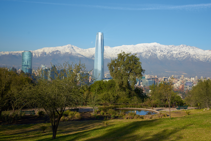 Snow covered mountains surrounding the modern high rise buildings of Santiago, the capital of Chile. View from Cerro San Cristobal.