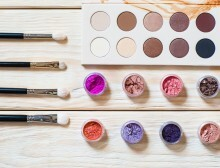 set of professional brushes for a make-up of eyes, a palette of nude colored eyeshadows and colorful pigments on a wooden background. set of the professional makeup artist