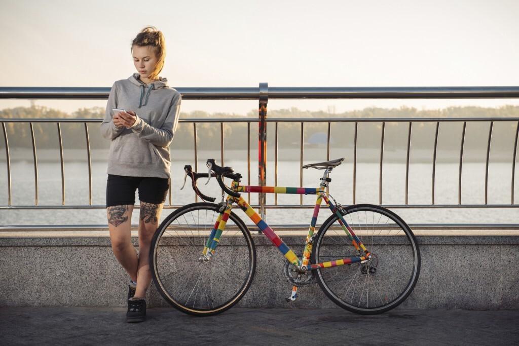 Ciclista checando o smartphone com a bicicleta parada ao lado