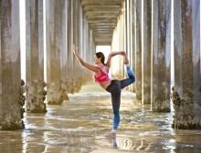 Mulher fazendo asana de yoga na praia