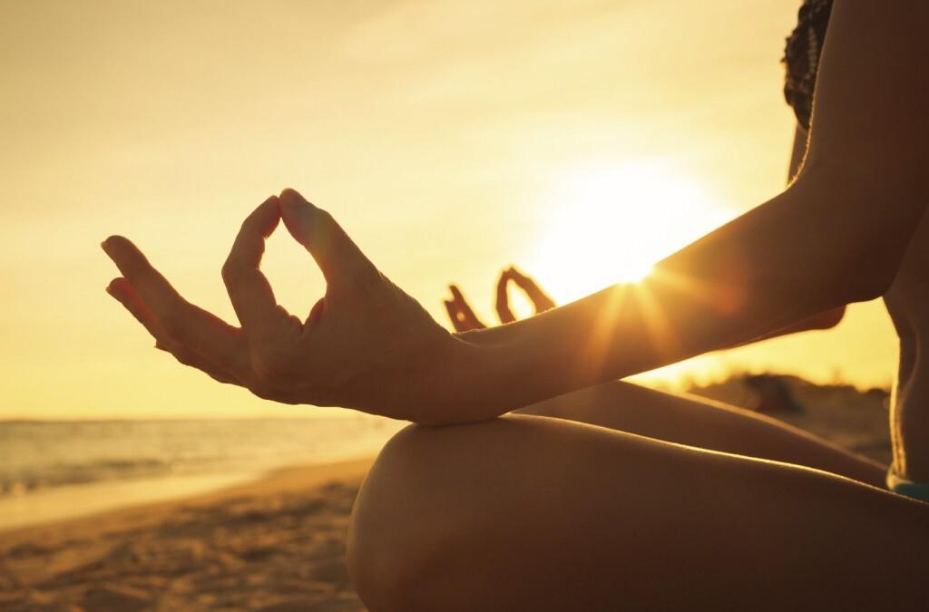 Pessoa meditando ao pôr do sol