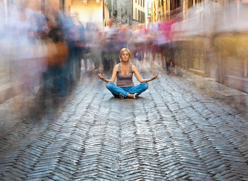 Mulher meditando em local barulhento