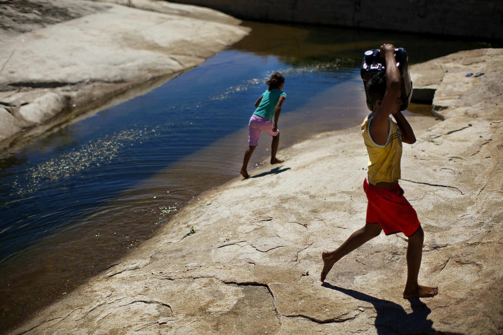 Crianças retiram água de  tecnologia social aplicada pelo Cepfs no Nordeste; crédito: Na Lata