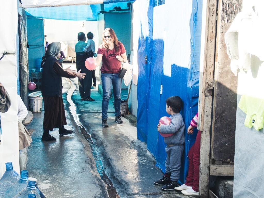 A jornalista Talita Ribeiro entrega balões a refugiados em campo no Curdistão Iraquiano