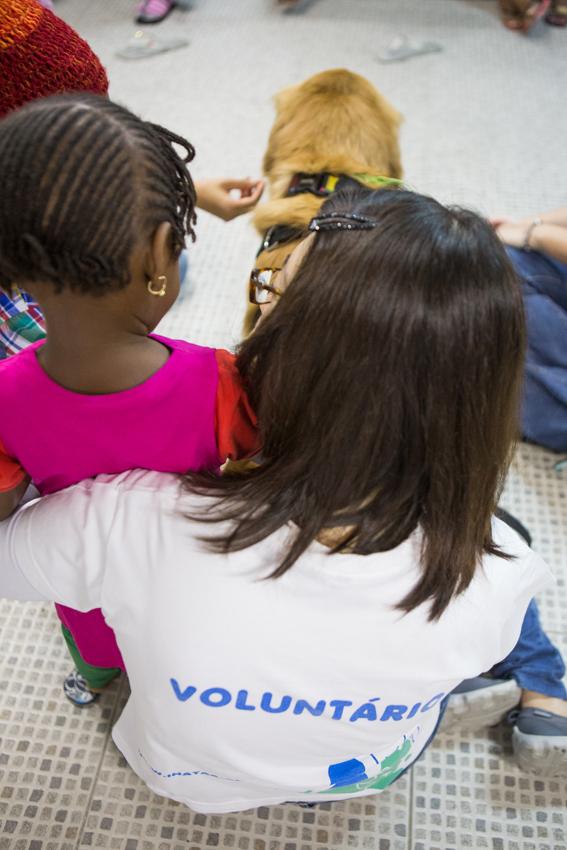 Voluntária do Inataa e menina refugiada fazem carinho em cão durante visita