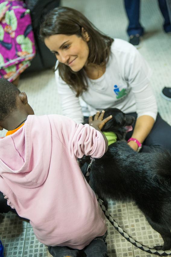 Garoto acaricia cachorro voluntário do Inataa, observado por membro da equipe