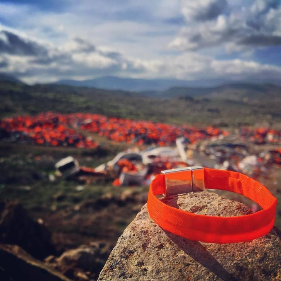 Milhares de coletes salva-vidas usados por refugiados para chegar à Grécia; em primeiro plano, a pulseira Zoë Band