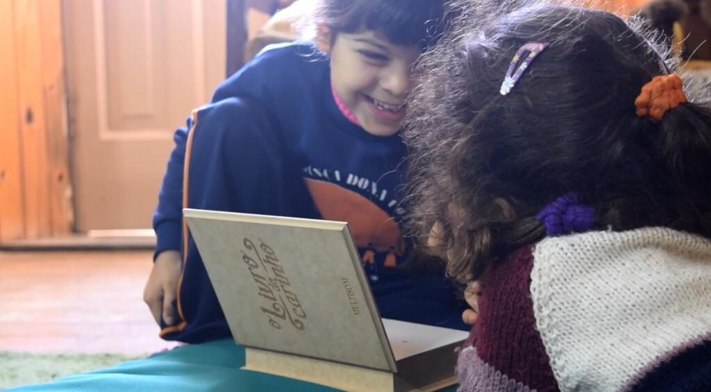 Crianças brincam com livro que as conecta com pessoas do Lar de Idosos Filadélfia