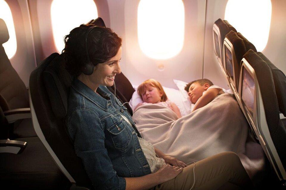 Mãe sorridente assiste à TV no avião enquanto dois filhos dormem um ao lado do outro em assentos de avião